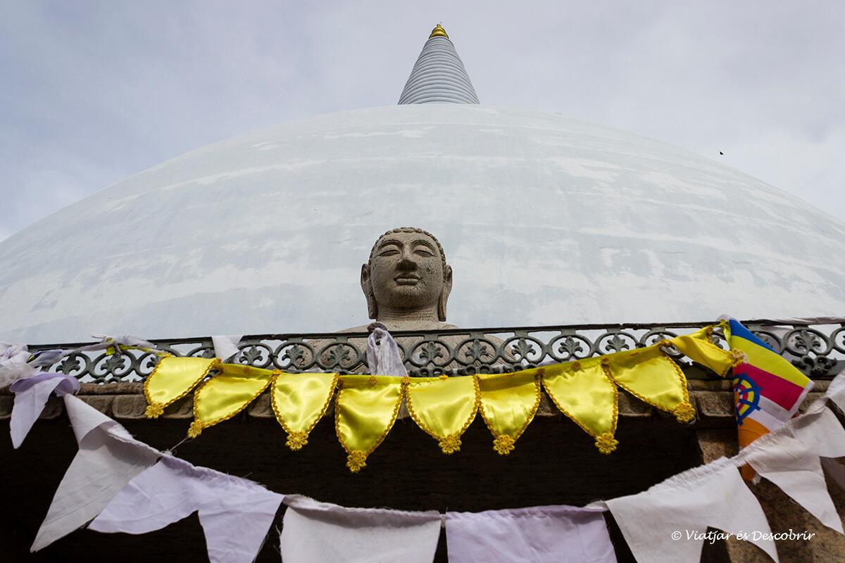 buda esculpida al lado de una estupa en anuradhapura