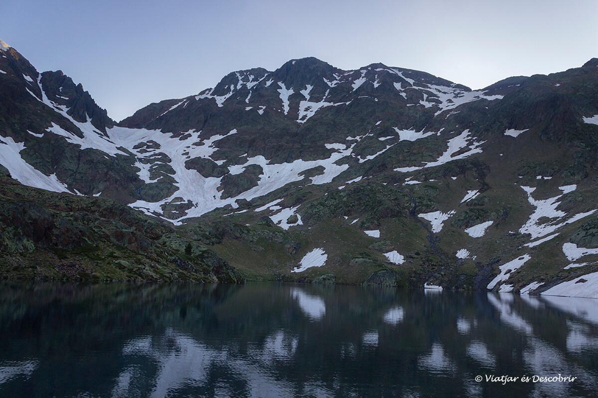 reflejos bajo la hora azul cuando empezaba amanecer frente el estany d'estats en el pirineo
